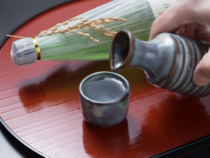 徳利からお猪口に日本酒を注ぎ終えた男性